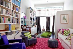 Former salesroom converted into spacious living room with colourful accessories and tall bookcases against wall