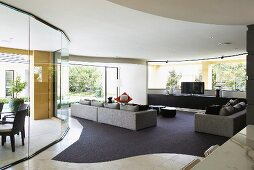 Cubic sofa set on rug with curved edges next to curved glass partition in spacious modern living room