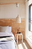Pendant lamp with wicker lampshade above side table next to bed against wall with rustic wooden panel in sunny bedroom