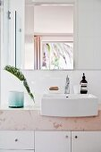 Modern washstand with stone top, base cabinets, white countertop sink and palm frond in vase