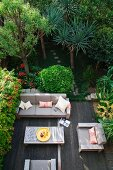 View down onto wooden deck with modern table and sofa set in densely planted garden