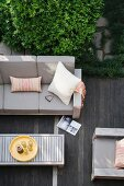 View down onto grey-upholstered outdoor furniture and coffee table on wooden terrace