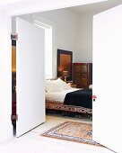 View through open double doors into bedroom with Oriental-style bed and wardrobe