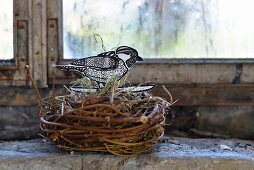 Hand-crafted paper bird in wicker birds' nest on windowsill