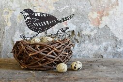 Hand-crafted paper bird and quail eggs in birds' nest on wooden surface against wall with peeling paint
