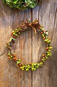 Wreath of rose hips on rustic wooden background