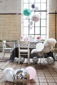 Vintage industrial interior used as party location with delicate, romantic decorations and disco ball