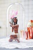Figurine of Caribbean girl holding delicate summer flower under glass cover on white doily