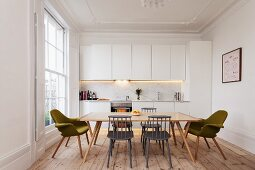 Simple, white fitted kitchen in renovated period apartment with lattice window, wooden floor and retro-style dining area