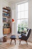 Gemütliche Leseecke vor Sprossenverglasung mit grauem Retro-Ohrensessel und passender Fußbank, orangefarbene Stehleuchte und Bücherregal in der Nische