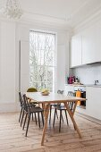 Simple white fitted kitchen in renovated period building with floor-to-ceiling lattice window, stripped wooden floor and retro dining set