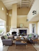 Grey sofa and armchairs around wooden coffee table in double-height interior with fireplace