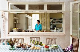 Bread and cheese on table, simple wooden chairs on veranda in front of open window with view of woman in kitchen