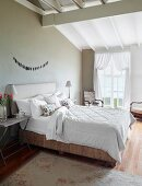 Double bed at comfortable height with upholstered headboard against taupe wall in elegant bedroom with rustic charm
