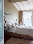 View through open door of double bed at comfortable height in rustic bedroom with taupe walls