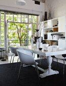 White dining table with turned legs and modern shell chairs on black rug in front of open balcony doors with view of courtyard