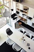 View down onto white dining table with modern chairs and shelving with integrated desk