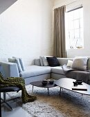 Pale grey corner sofa and set of coffee tables on flokati-style rug in corner