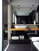 Modern bathroom - wooden washstand with counter-top basin, large mirror and large, black floor tiles