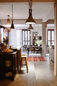 Open-plan, vintage living-dining area with kitchen counter, bar stools, wooden louver blinds and industrial lamps