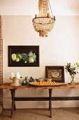 Rustic wooden table decorated with ceramics, china, vase of flowers and dish of fruit below framed still-life artworks and chandelier
