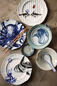 Arrangement of various plates and bowls artistically painted with Oriental animal motifs, ceramic spoon and chopsticks