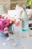 Roses of various colours in enamel pot, glass of water and vintage swing-top bottle on table