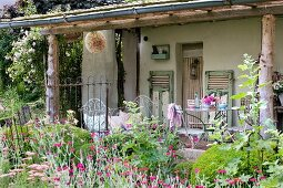 Flowering garden in front of old house with roofed veranda and various vintage metal furnishings