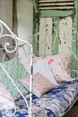 Various cushions with romantic patterns on vintage metal couch