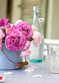 Bouquet of roses in enamel pot and glass on table
