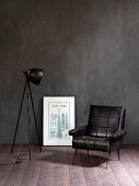 Retro leather armchair, black studio lamp and picture leaning against wall