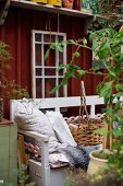 Scatter cushions and basket on wooden bench painted pale grey in front of simple wooden cabin