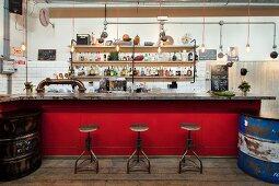 Red bar counter and vintage stools in front of bottles on shelves in former workshop