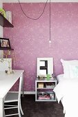 Bedroom with bed, bedside table & desk in front of wall with purple patterned wallpaper