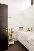 View into modern bathroom with white washstand, base units & mirrored wall
