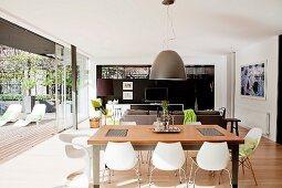 Open-plan interior with floor-to-ceiling, open sliding doors leading to sun terrace