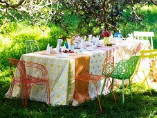 Table set with various tablecloths and colourful metal chairs on lawn in garden