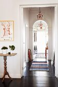 View along narrow hallway with dark wooden floor, arch & striped rugs