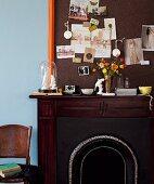 Farblich angepasste Pinnwand auf dunkelbraunem Kaminsims mit Kartensammlung, Blumen und ausgewähltem Kunsthandwerk