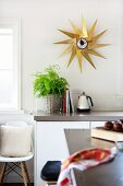 View across counter of kitchen unit below star-shaped, brass wall clock and classic shell chair below window