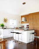 Delicate bar stools at free-standing kitchen island in open-plan, modern kitchen with wooden fronts