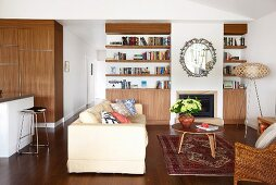 Pale couch and 50s-style coffee table on rug in modern, open-plan interior