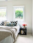 View though open door of modern bed with scatter cushions and cubic side table below window