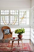 Vase of flowers on low, 50s-style side table and wicker chair in front of window with art nouveau glazing