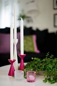 Set of pink and white candlesticks and tealight holders next to bowl of leafy twigs
