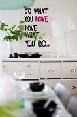Table lamp with white lampshade and leafy twigs in vase on chest of drawers below motto on wall and behind set table