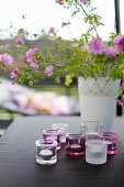 Bouquet of purple flowers in white vase and tealight holders on black tablecloth on table