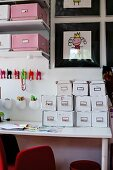 White card index boxes on desk below colourful hooks and shelves of pink and white file storage boxes