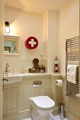 Toilet and washstand against half-height wood-panelling in bathroom with first-aid cabinet on wall