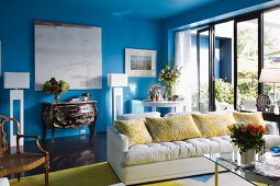 White sofa next to glass terrace doors in front of Rococo chest of drawers against blue wall in living room